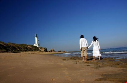 Couple at the beach walking towards the lighthouse