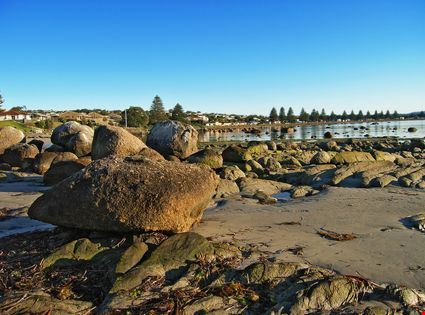 Early morning view of large rocks and sand at the waterfront