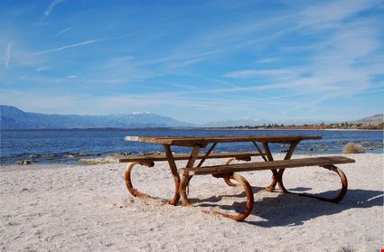 Old picnic table on beach along lake