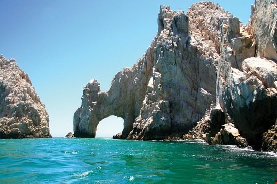 Amazing natural arch in mountain with blue sea and sky