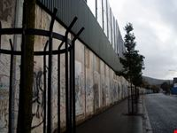 belfast il muro tappezzato di scritte e sovrastato da ulteriori barriere
