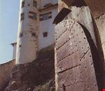Dall'antico portone corazzato della cinta muraria esterna, una delle torri di guardia di Castel Bragher